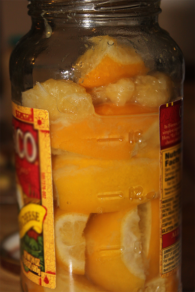 Opened jar of preserved lemons with soft rinds ready to cook with